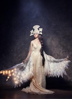 Art woman ange avec des ailes dans une robe longue de luxe