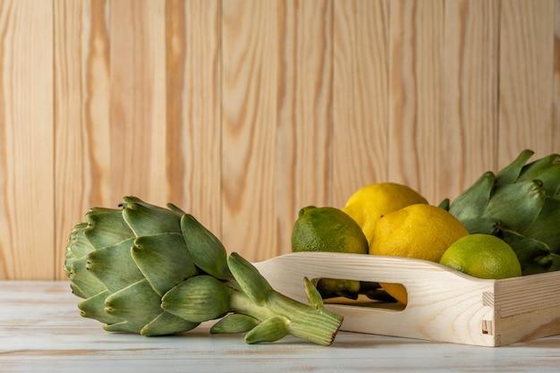 Artichauts biologiques mûrs sur une table en bois blanche avec du citron.