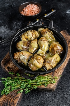 Artichauts en conserve dans l'huile d'olive sur une table de cuisine en bois rustique. fond noir. vue de dessus.