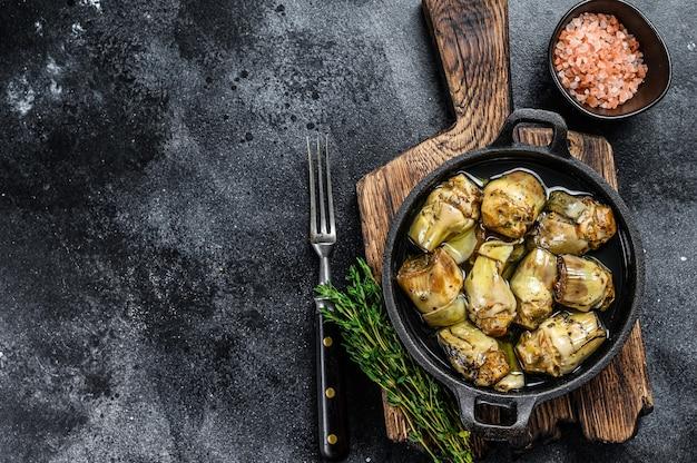 Artichauts en conserve dans l'huile d'olive sur une table de cuisine en bois rustique.