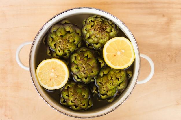 Artichauts cuits au citron et sel dans la cocotte avec de l'eau