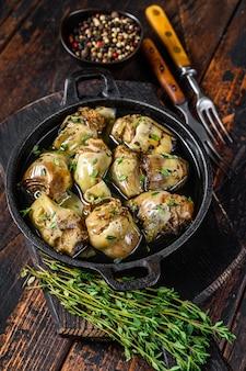 Artichauts marinés à l'huile d'olive dans une poêle.