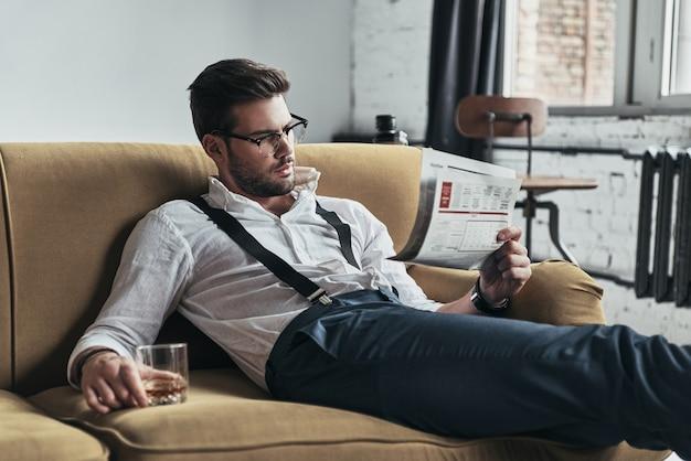 Article intéressant. jeune homme élégamment vêtu, lisant un journal et tenant un verre assis sur un canapé