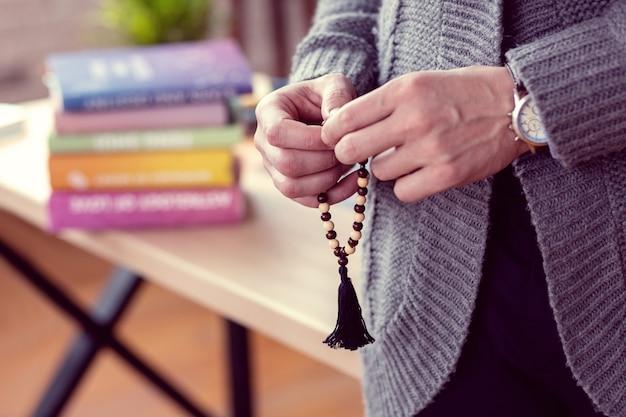 Article spécial. mise au point sélective d'une chaîne de perles étant entre les mains des hommes lors d'une séance de bonne aventure