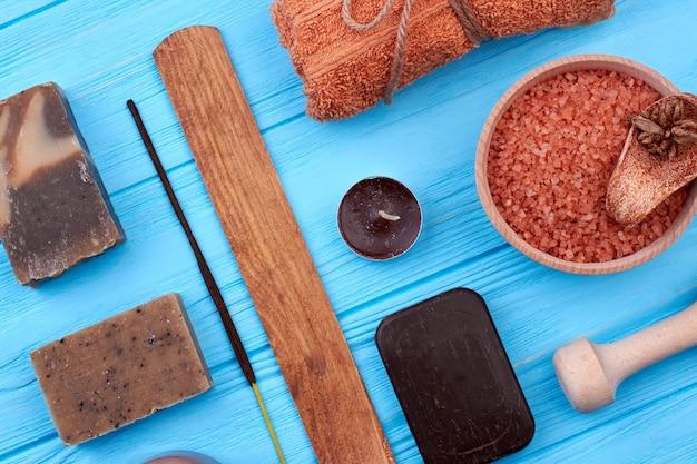 Articles bruns pour un traitement spa sur un bureau en bois bleu. savon avec bougie et sel vue de dessus à plat.