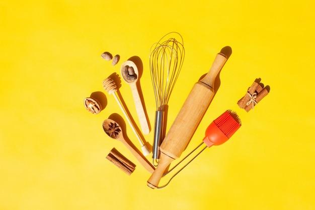 Articles de cuisine pour cuisiner. fouet, cuillères en bois, noix et cannelle sur fond jaune