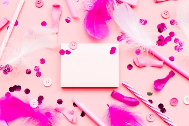 Articles décoratifs avec bloc-notes vide sur fond rose
