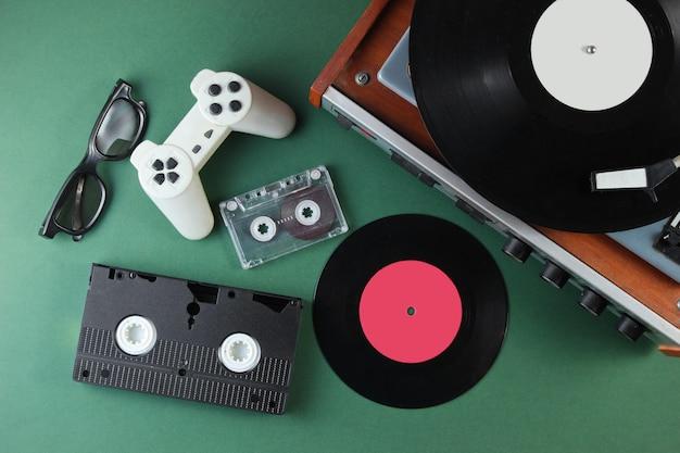 Articles de médias et de divertissement rétro des années 80. lecteur vinyle, vidéo, cassettes audio, lunettes 3d, manette de jeu sur surface verte.