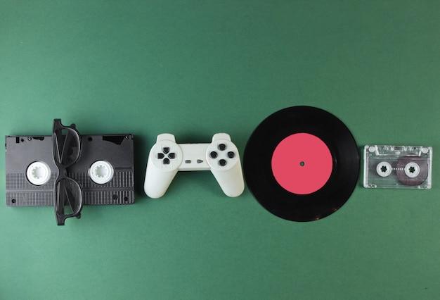 Articles de médias et de divertissement rétro des années 80. plaque de vinyle, vidéo, cassettes audio, lunettes 3d, manette de jeu sur surface verte.
