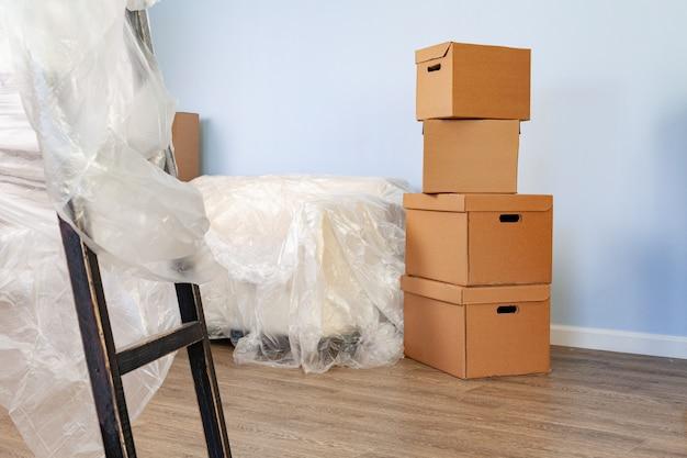 Des articles ménagers emballés dans des boîtes et un canapé emballé pour le déménagement