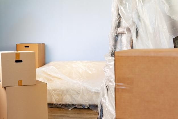 Des articles ménagers emballés dans des boîtes et un canapé rempli pour le déménagement