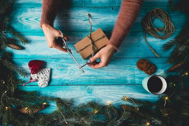 Articles de noël sur une table wodden bleu. mains de la femme enveloppant le cadeau de noël.