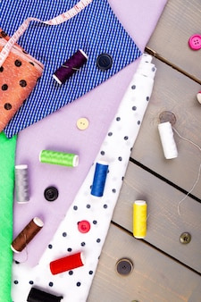 Articles pour coudre des vêtements. boutons à coudre, bobines de fil et de tissu. vue de dessus.