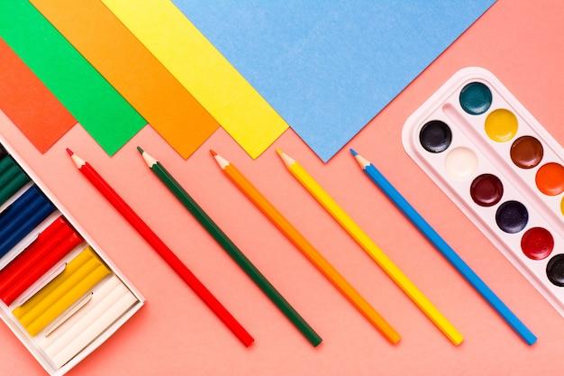 Articles pour la créativité: feuilles de carton, crayons de couleur, pâte à modeler et aquarelle de couleur rouge. vue de dessus