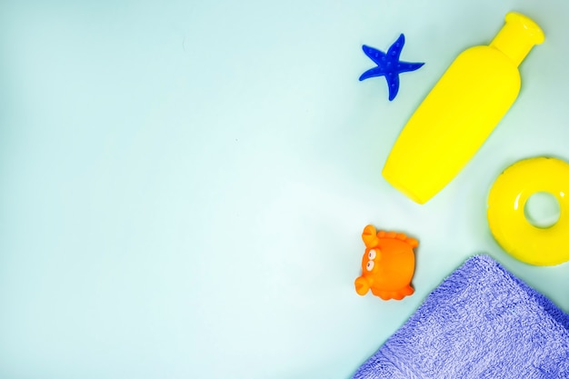 Articles pour enfants pour le bain : shampoing, serviette, jouets étoiles de mer, bouée de sauvetage, crabe, sur fond bleu. produits de bain à plat. soins bébé. espace de copie.