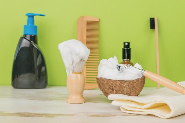 Articles pour se raser, se laver et se peigner sur une table en bois sur fond vert.