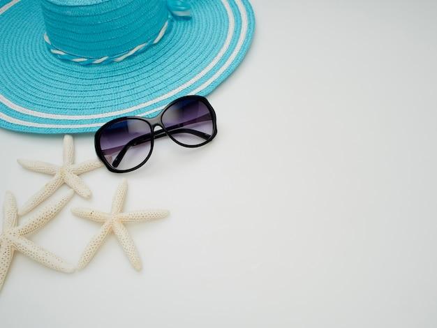 Articles de robe de plage d'été - coquillages, étoiles de mer, lunettes de soleil, chapeaux de paille sur fond blanc