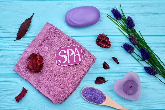 Articles de salle de bain spa sur un bureau en bois bleu vue de dessus à plat. savon avec bougie et fleurs.