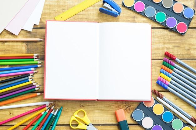 Les articles scolaires font un cadre sur fond en bois