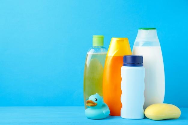 Articles de toilette bébé sur fond bleu. gel douche bébé. vue de dessus
