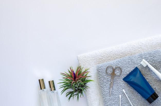 Articles de toilette pour hommes dans un style de vie moderne sur des serviettes avec des plantes aériennes tillandsia sur blanc.