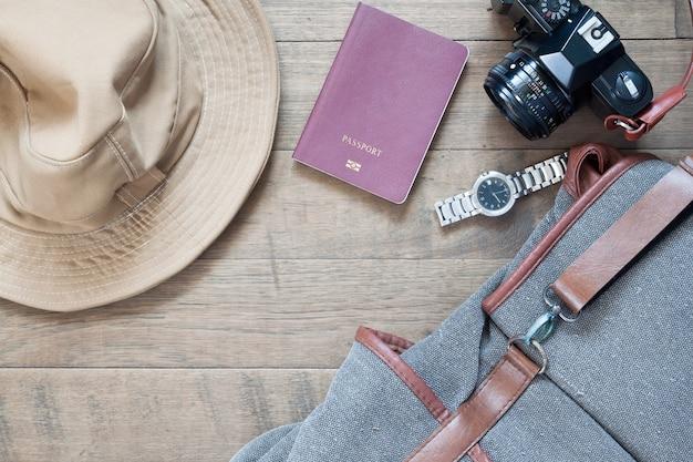 Articles de voyage et accessoires avec appareil mobile sur fond en bois, plat