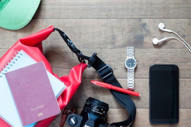 Articles de voyage et accessoires avec dispositif mobile sur fond de bois, collection d'été plat