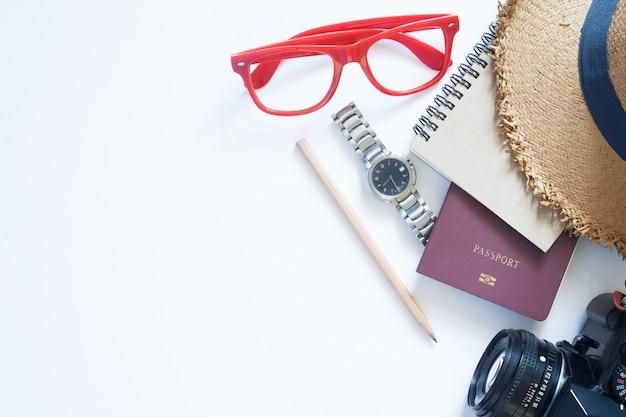 Articles de voyage, passeport, appareil photo, cahier, montre et chapeau sur fond blanc avec copie