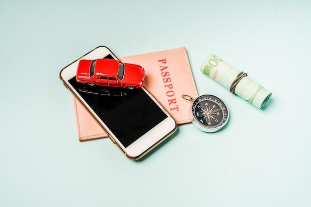 Articles de voyage une petite voiture et passeports sur fond bleu. contexte pour le concept de vacances