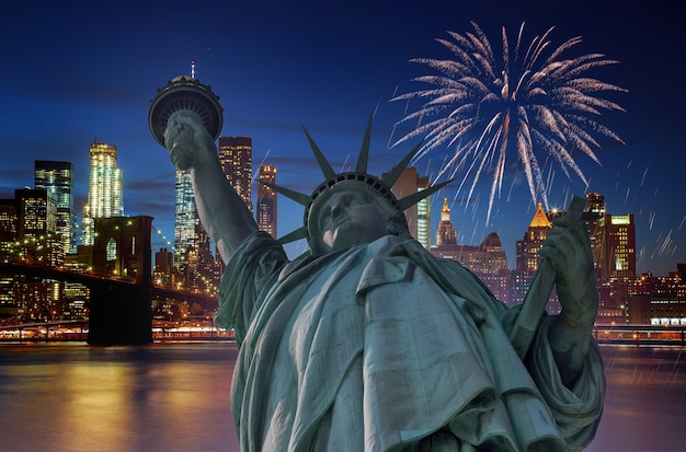 D'artifice au-dessus de la ville de manhattan ny la nuit avec la statue de la liberté à manhattan new york city usa célébrant le jour de l'indépendance des usa