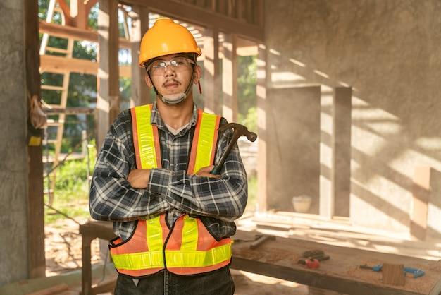 Artisan asiatique tenant un marteau dans les mains, debout dans un atelier spacieux et regardant la caméra sur un chantier de construction