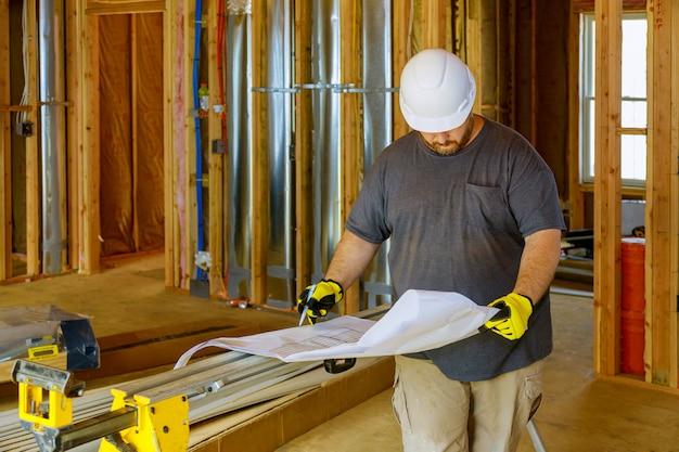 Artisan, bâtiment vérifiant un plan sur une construction de maison en construction