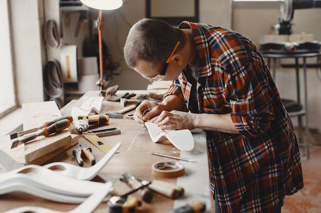 Artisan coupant une planche en bois