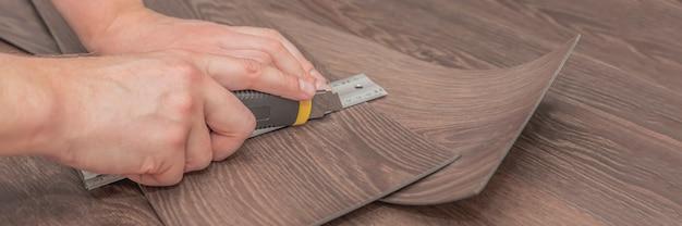 Un artisan coupe une planche de vinyle avant l'installation, une bannière en gros plan
