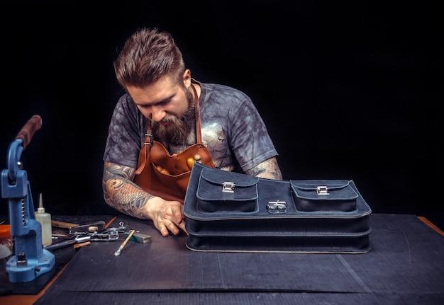 Artisan du cuir crée des produits en cuir de qualité sur son lieu de travail.
