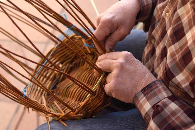 Artisan fabriquant un panier en osier