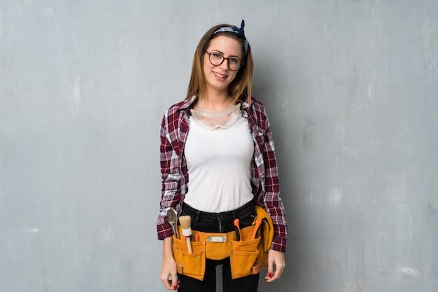Artisan ou femme électricien avec des lunettes et heureux