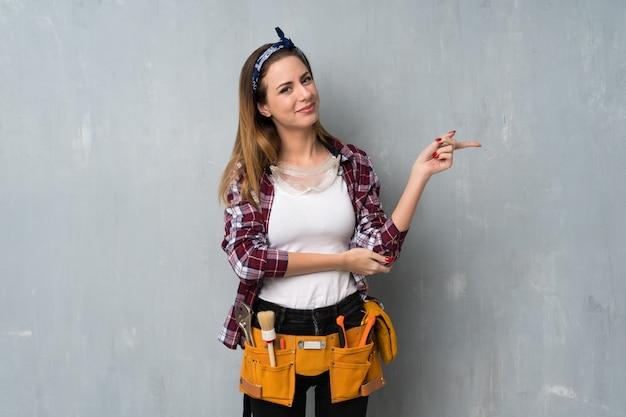 Artisan ou femme électricien montrant un doigt sur le côté