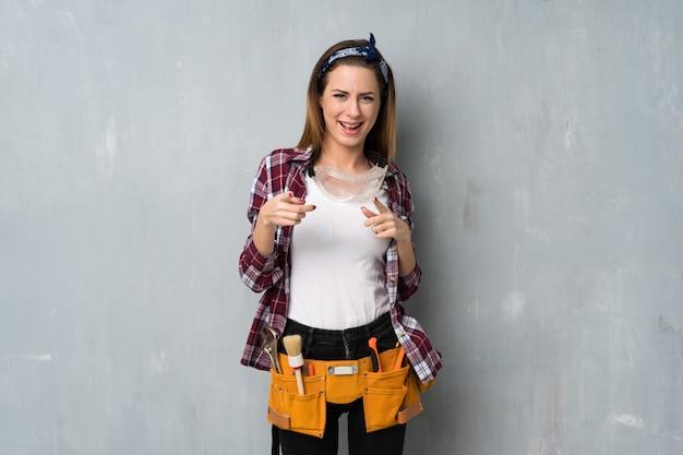 Artisan ou femme électricien pointant vers l'avant et souriant