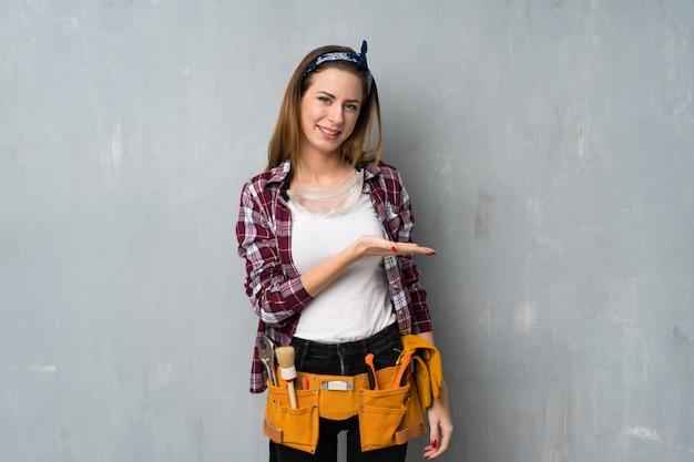 Artisan ou femme électricien présentant une idée tout en regardant en souriant