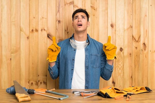 Artisan homme sur bois pointant avec l'index une excellente idée