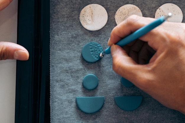 Artisan méconnu fabriquant des boucles d'oreilles colorées avec de l'argile et créant un dessin.
