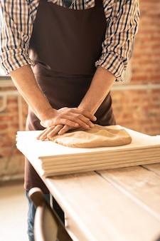 Artisan potier contemporain en vêtements de travail debout par table en bois et pétrir l'argile sur pile de planches en atelier