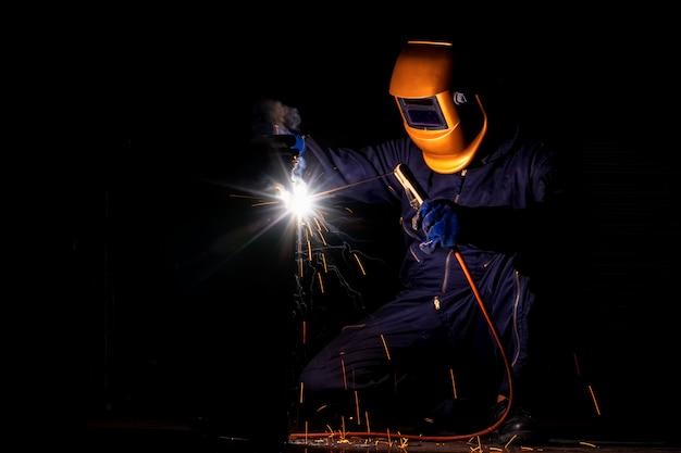 Un artisan soude avec de la pièce en acier. travailleur à propos de l'acier de soudeur utilisation de la machine de soudage électrique il existe des lignes de lumière qui sortent et des équipements de sécurité dans l'industrie industrielle.