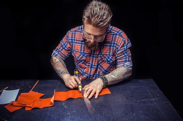 Un artisan travaillant le cuir crée une nouvelle maroquinerie dans son atelier de cuir.