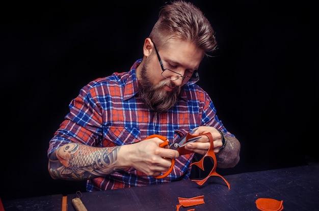 Artisan travaillant avec du cuir découpant des formes de cuir pour un nouveau produit dans sa boutique.