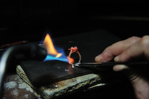 Artisan travaille en utilisant un outil de pulvérisation de gaz pour faire un anneau