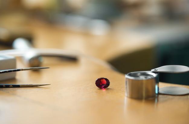 Artisanat de bijoux. pince à épiler de bijoutier, loupe, pierre précieuse rubis. les outils de graveur bijoutier sur un bureau vintage en bois.