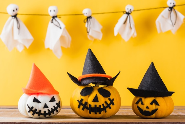 Artisanat fantôme blanc visage effrayant suspendu et tête de citrouille halloween jack lanterne sourire et araignée sur bois