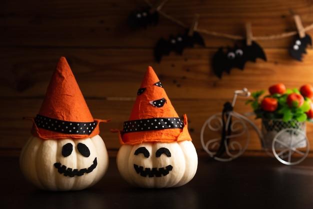 Artisanat d'halloween, citrouille blanche portant chapeau de sorcière avec chauve-souris sur table en bois